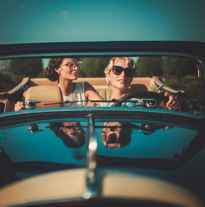 Duas senhoras à moda em um convertible clássico fotos de stock