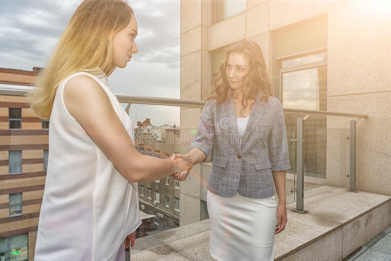 Duas senhoras do negócio no terraço das mãos da agitação do centro de negócios para assinar um negócio Louro na blusa branca, mor imagens de stock royalty free