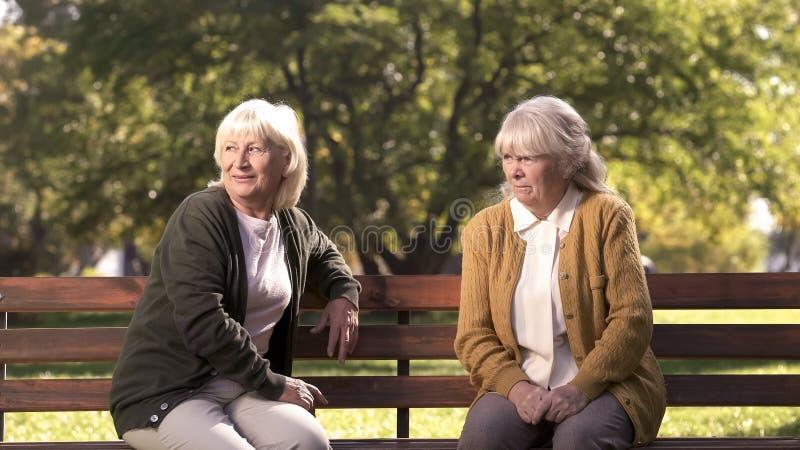 Duas senhoras idosas mal-humoradas que julgam os povos do transeunte, sentando-se no banco no parque, pensão fotografia de stock royalty free