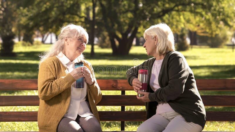 Duas senhoras idosas que bebem o chá quente das canecas do curso, sentando-se no banco no parque ensolarado fotos de stock royalty free