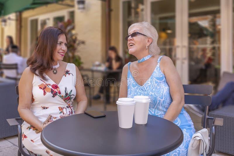 Duas senhoras maduras apreciam uma xícara de café no café exterior imagem de stock