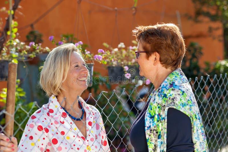 Duas senhoras superiores que conversam no jardim imagens de stock royalty free