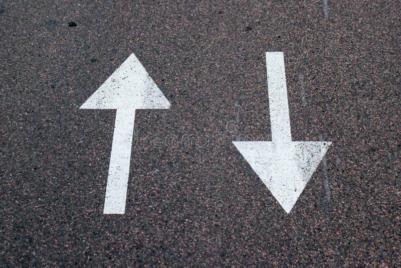 Duas setas no asfalto Sinal da rua em dois sentidos foto de stock