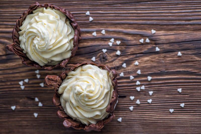 Duas sobremesas do chocolate encheram-se com o creme branco na tabela de madeira, sobremesa com corações brancos para o dia de Va fotos de stock