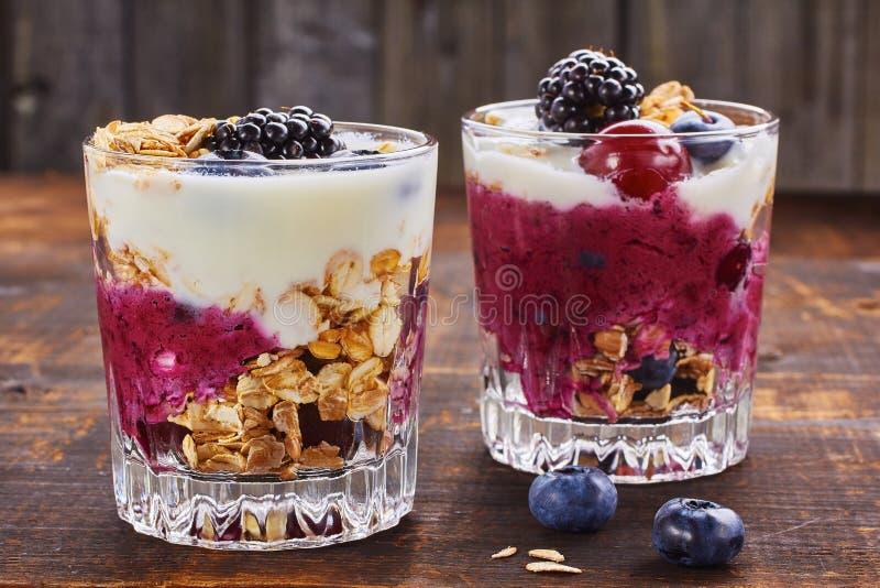 Duas sobremesas do iogurte com bagas e muesli fotos de stock