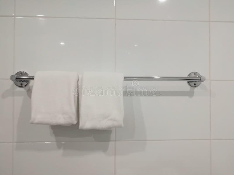 Duas toalhas brancas estão pendurando no banheiro imagem de stock