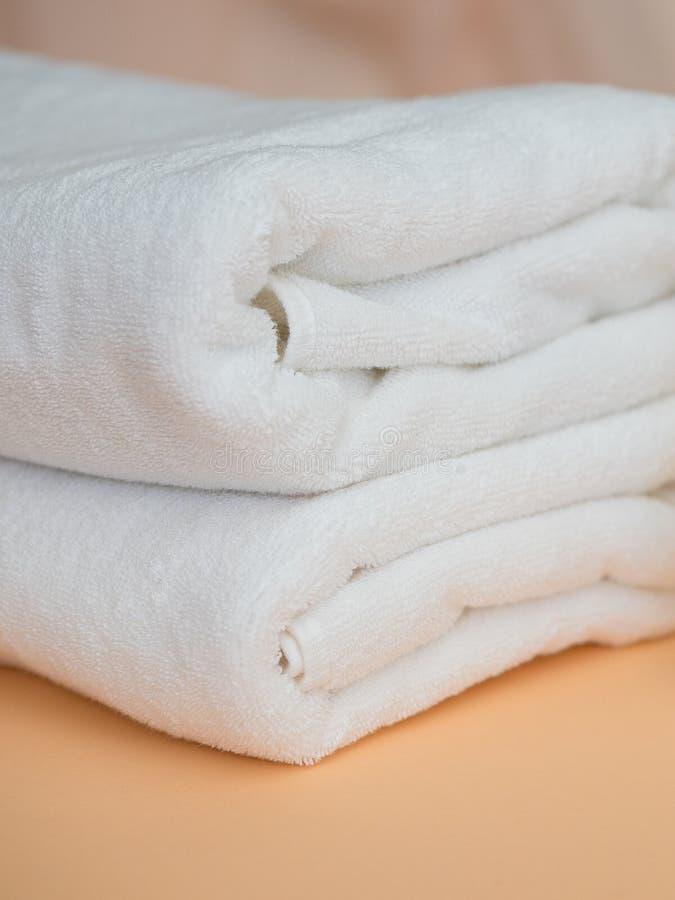 Duas toalhas brancas no fundo alaranjado, vertical Tema da limpeza e da higiene imagens de stock