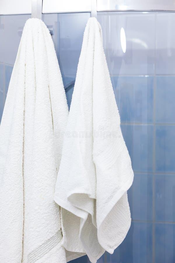Duas toalhas brancas que penduram em portas do chuveiro foto de stock royalty free