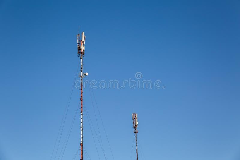 Duas torres do telefone contra um céu azul claro imagem de stock royalty free