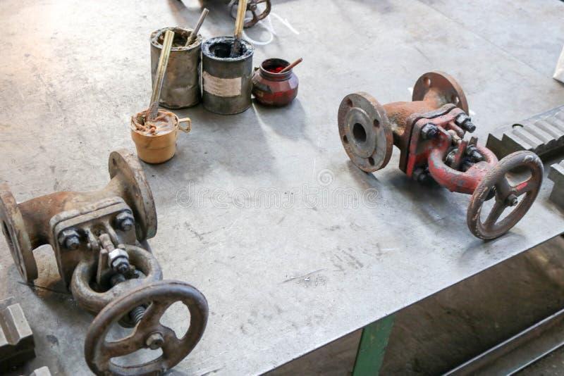 Duas travas velhas do metal, encaixes do encanamento, latas com graxa da grafite, óleo contínuo na fábrica fotos de stock royalty free