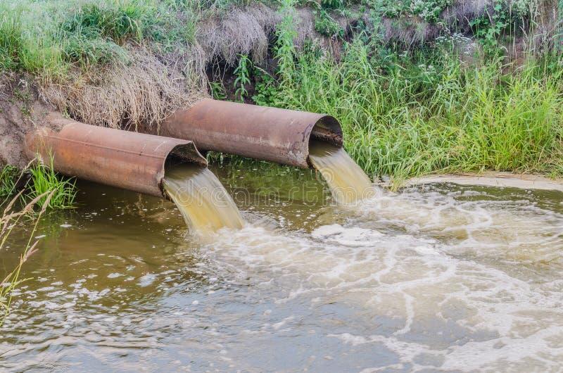 Duas tubulações de esgoto derramam para fora ao rio/água que jorra do esgoto ao rio imagens de stock royalty free