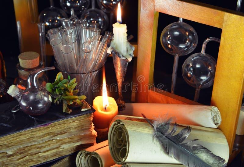 Duas velas com garrafas e os livros mágicos imagens de stock royalty free