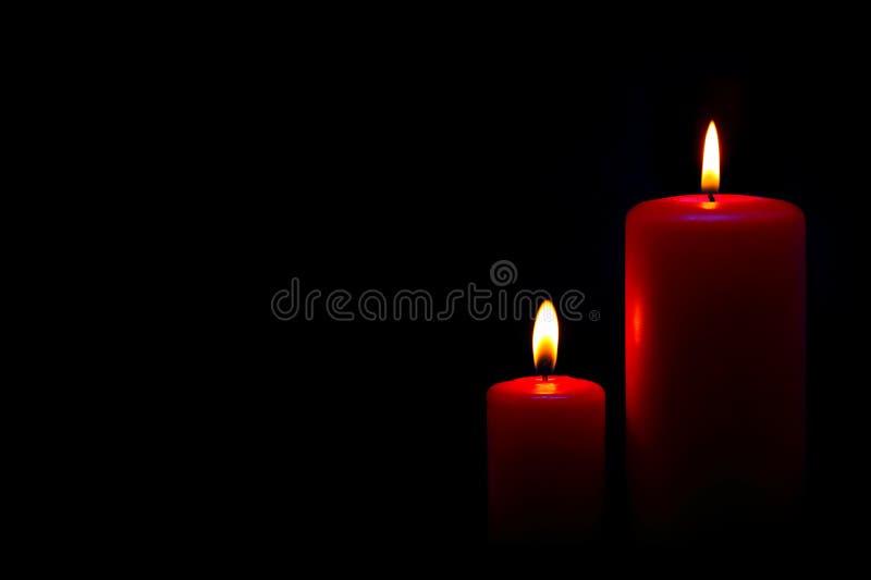 Duas velas vermelhas no preto foto de stock