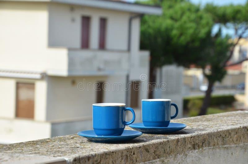 Duas xícaras de café azuis com vista panorâmica de uma cidade no fundo no balcão contra o contexto do velho fotografia de stock