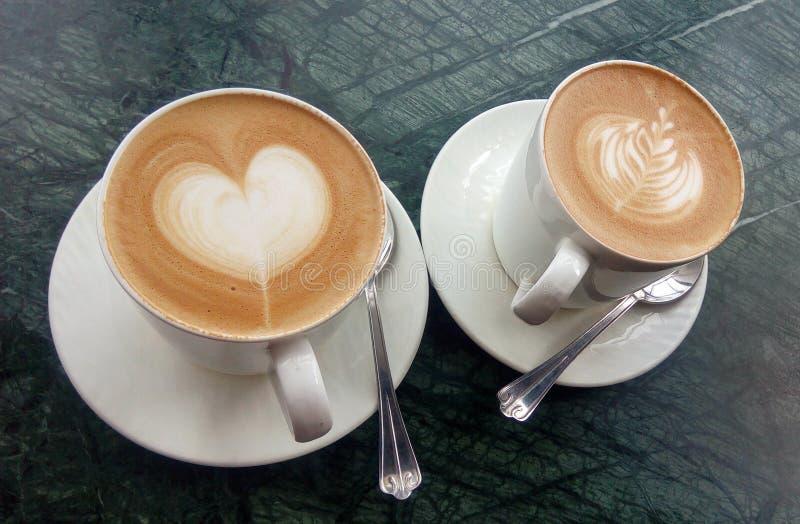 Duas xícaras de café em uma tabela com coração e folha da arte do latte fotografia de stock