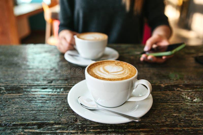 Duas xícaras de café em uma tabela de madeira, uma moça que guarda um telefone em sua mão e que vai chamar Esperando uma reunião foto de stock