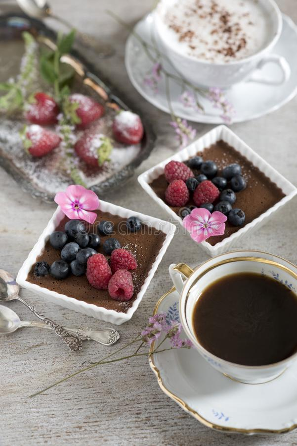 Duas xícaras de café, sobremesas do chocolate e morangos, cutelaria do vintage imagem de stock