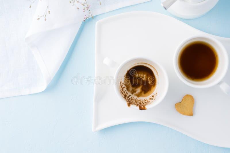 Duas xícaras de café vazias e cookie dada forma coração foto de stock