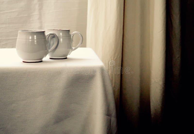Duas xícaras de chá brancas em uma tabela branca contra um fundo branco foto de stock royalty free