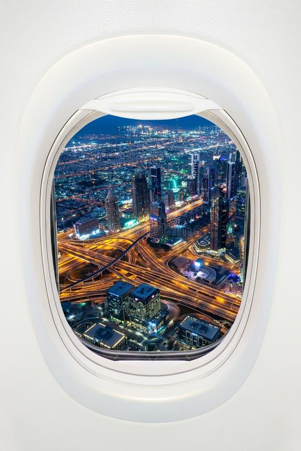 Dubai à noite visto pela janela do avião viajar nos Emirados Árabes Unidos imagem de stock