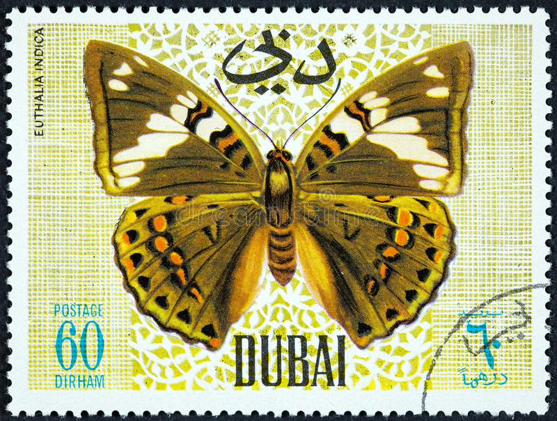 A stamp printed by Dubai, shows Butterfly, Euthalia Indica stock images