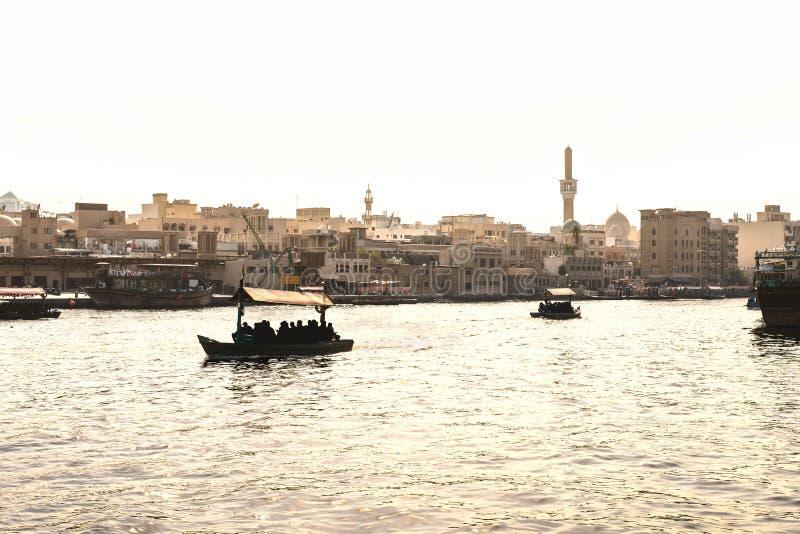 Dubai Creek con los barcos del abra Gente y turistas locales que usan el taxi y el transbordador del agua en el río viejo de la c imágenes de archivo libres de regalías