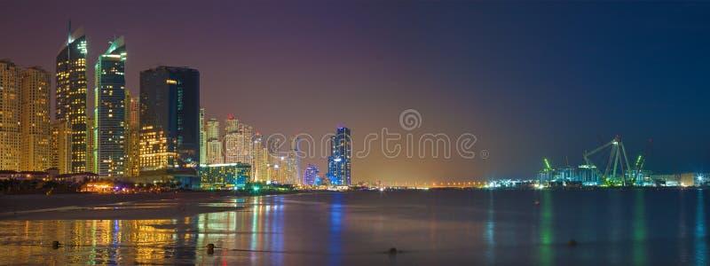 Dubai - das nächtliche Skylinepanorama von Jachthafentürmen und Weltvon größtem Riesenrad im Bau lizenzfreies stockfoto