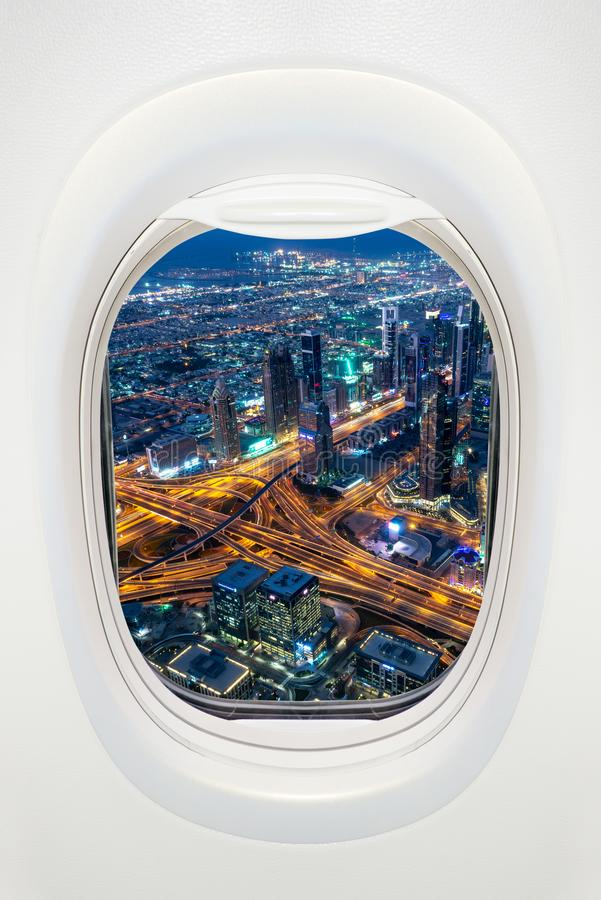 Dubai in der Nacht durch das Fenster der Flugreise im VAE-Konzept stockbild