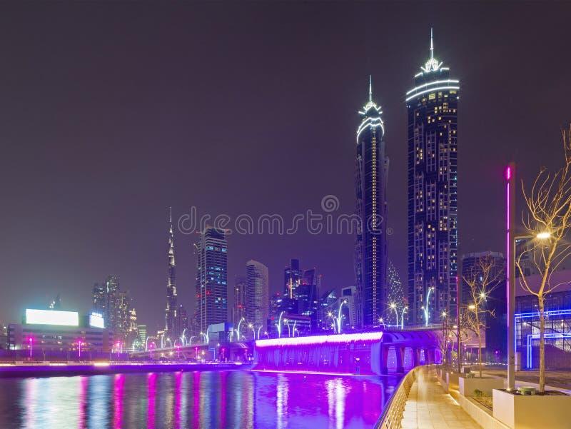 Dubai - die nächtlichen Skyline über dem Kanal und in die Stadt mit dem Wasserfall auf der Brücke lizenzfreie stockfotografie