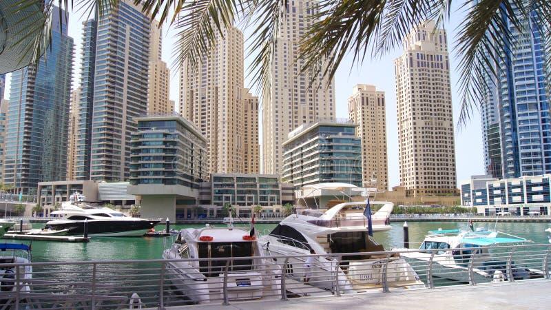 DUBAI, EMIRATOS ÁRABES UNIDOS - 2 de abril de 2014: Vista em arranha-céus do porto de Dubai e no porto o mais luxuoso do superyac imagem de stock