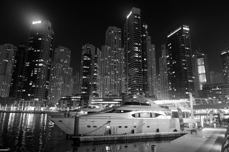Dubai, Emiratos Árabes Unidos - 26 de dezembro de 2017: yacht club no distrito do porto de Dubai na noite Barco do iate na skylin foto de stock