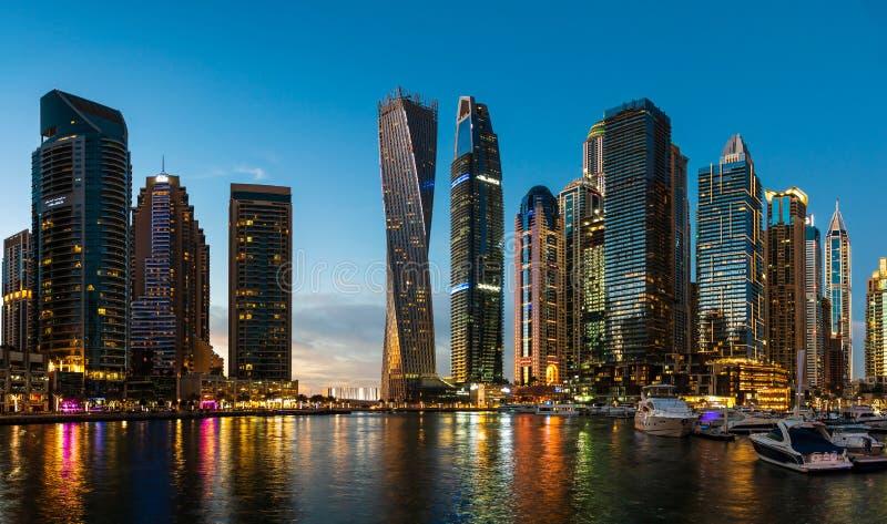 Dubai, Emiratos Árabes Unidos - 14 de fevereiro de 2019: Arranha-céus modernos do porto de Dubai e iate luxuosos na hora azul foto de stock royalty free