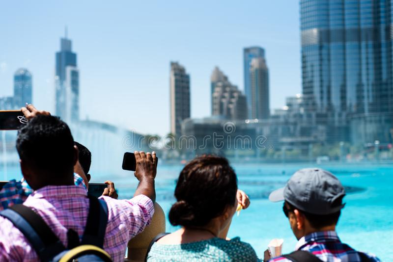 Dubai, Emiratos Árabes Unidos - 26 de março de 2018: Os povos recolhem em torno da fonte da alameda de Dubai para ver a mostra da fotografia de stock