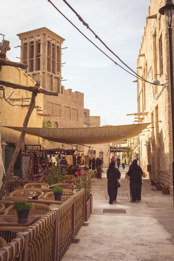 Dubai, Emiratos Árabes Unidos - 28 de março de 2019: Uma das ruas de Al Seef Heritage District com passeio de mulheres árabes imagens de stock royalty free