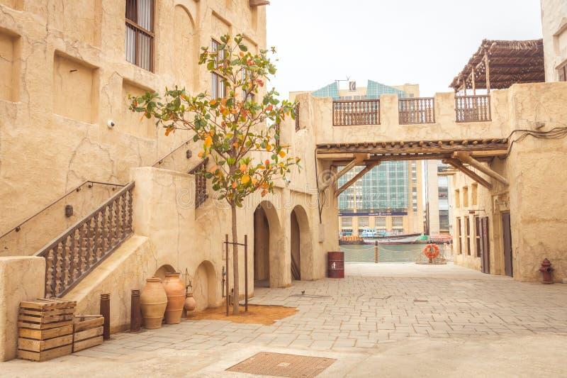 Dubai, Emiratos Árabes Unidos - 28 de março de 2019: Uma das ruas de Al Seef Heritage District com uma vista em Dubai Creek imagens de stock royalty free