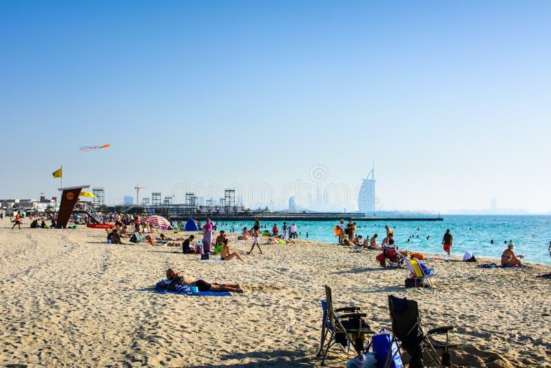 Dubai Förenade Arabemiraten, April 20, 2018: Drakestrand i Dubai med många besökare och det Burj Al Arab hotellet i bakgrunden royaltyfri foto
