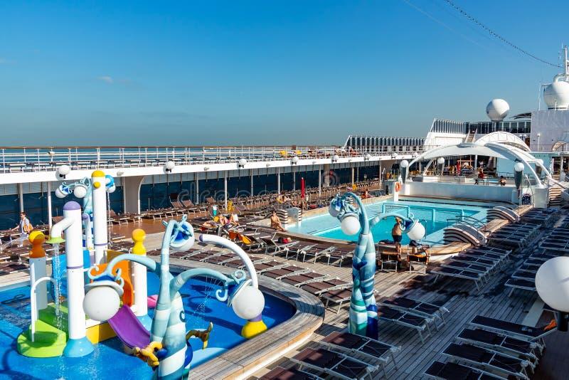 Dubai Förenade Arabemiraten - December 12, 2018: övredäck för kryssningskepp med simbassängen och vilapassagerare royaltyfria bilder
