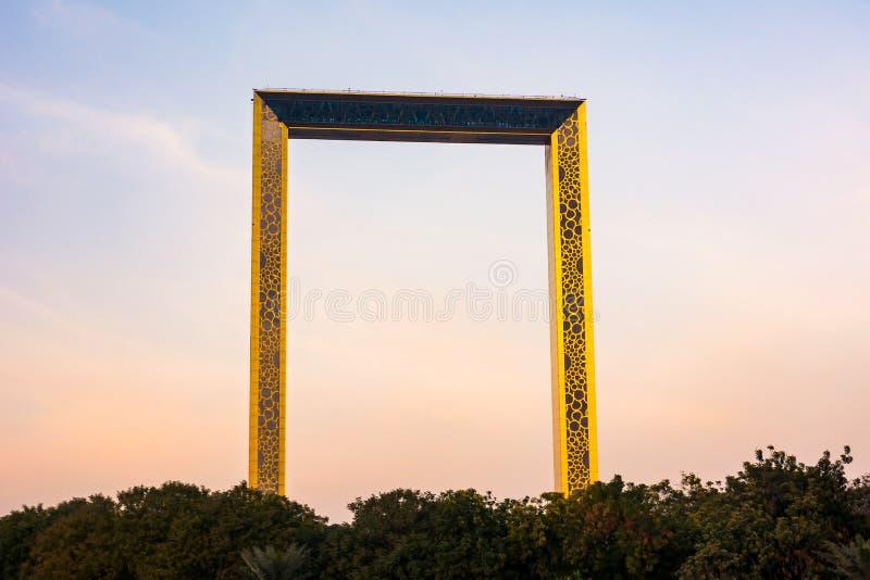 Dubai Förenade Arabemiraten, Februari 11, 2018: Dubai rambyggnad med palmträd på solnedgången Rammåtten som 150 meter är höga royaltyfria foton