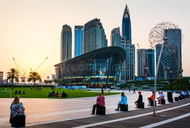 Dubai Förenade Arabemiraten - Maj 18, 2018: Folk som tycker om solnedgång med Dubai operabyggnad och moderna skyskrapor av Dubaie arkivbilder