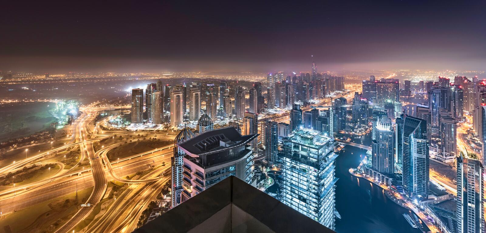 Dubai Horizon Lights Glowing in a hazy night with a beautiful panoramic Towers rooftop view stock photos