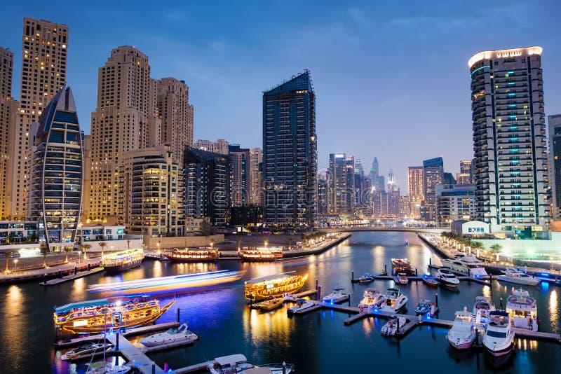 Dubai-Jachthafen mit Booten und Gebäude mit Toren nachts mit Lichtern lizenzfreie stockfotografie