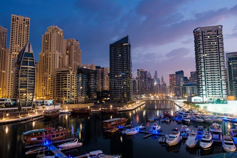 Dubai-Jachthafen mit Booten und Gebäude mit Toren nachts mit Lichtern und blauem Himmel stockfotografie