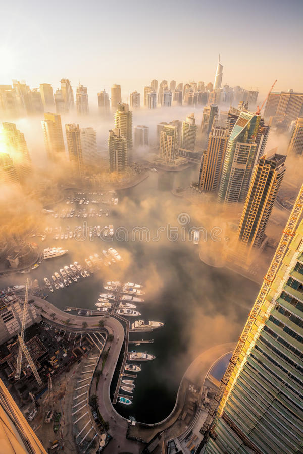 Dubai Marina is covered by early morning fog in Dubai, United Arab Emirates royalty free stock image