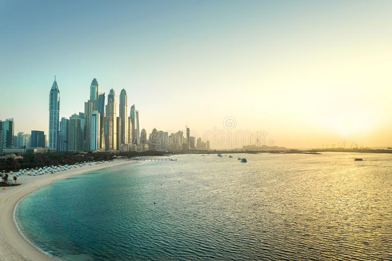 Dubai Marina at sunset. Panorama view of skyscraper buildings, beach, clear sky and sea at dawn. Scenic luxury city skyline. royalty free stock images
