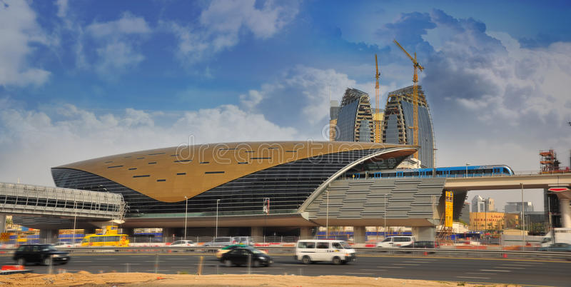 Dubai Metro Station and Metro Train. Dubai City with moving traffic in front of Dubai Metro Station. The train leaving the station, with white cloud background royalty free stock photography