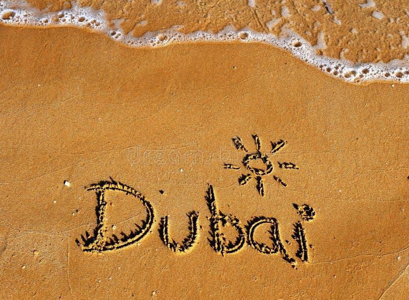 Dubai ord på sandstrandbakgrund arkivbild