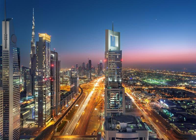 Dubai Sheikh Zayed Road por puesta del sol con las calles de la circulación densa fotografía de archivo