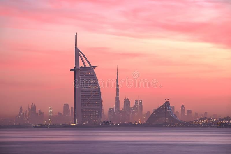 Dubai skyline lighted with beautiful sunrise colors. Stunning view of Dubai skyline from Jumeirah beach to Downtown lighted with warm pastel sunrise colors stock photos