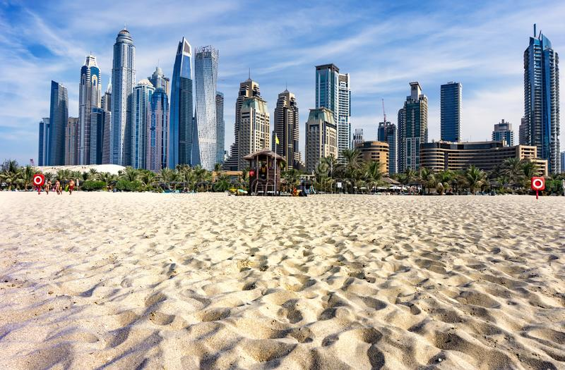 Dubai skyscraper skyline with palm trees and the sand of the beach stock photography