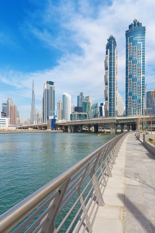 Dubai - The skyscrapers over and the promenade of new Canal and Burj Khalifa in the background stock photos